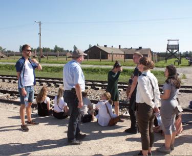 Elever sitter vid järnvägsspår.