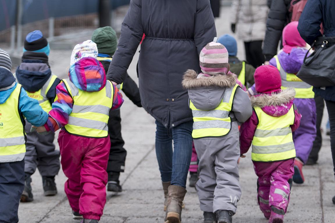 Pedagog håller i händer när barngruppen är ute.