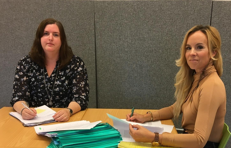 Två kvinnor vid bord med kompendium på.