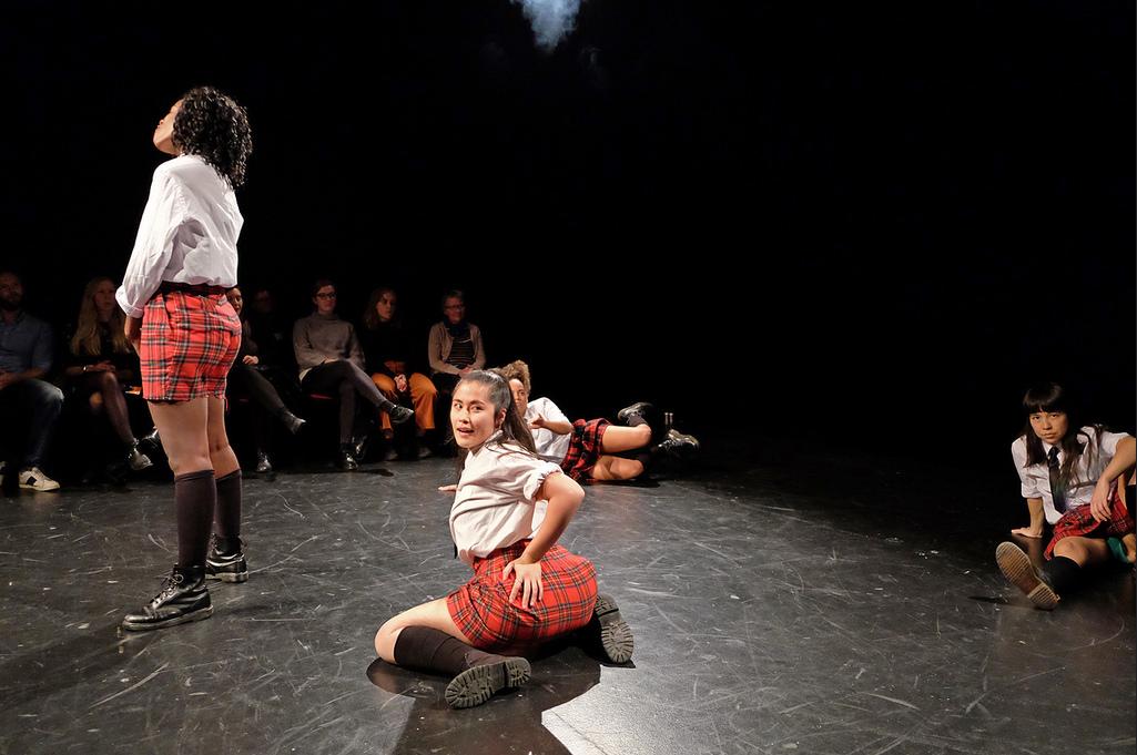 Kvinnor i skoluniform dansar.