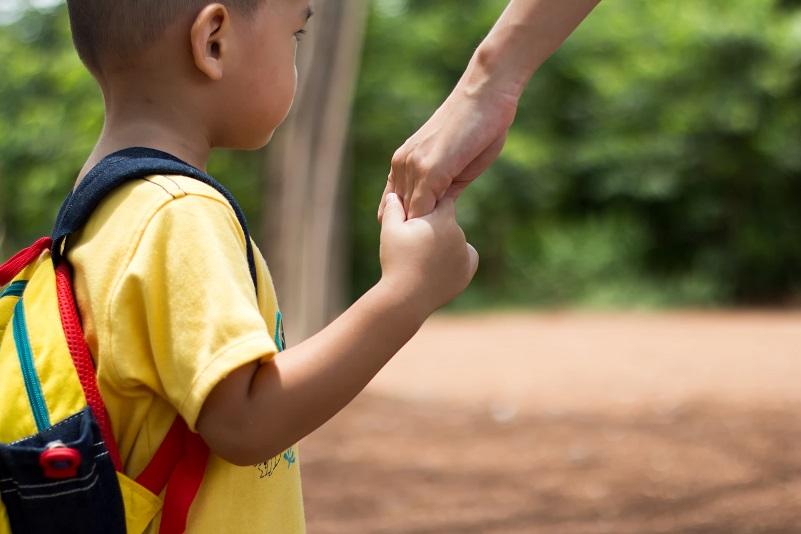 Barn håller vuxen i hand.