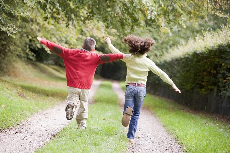 Två barn springer längs med grusväg.