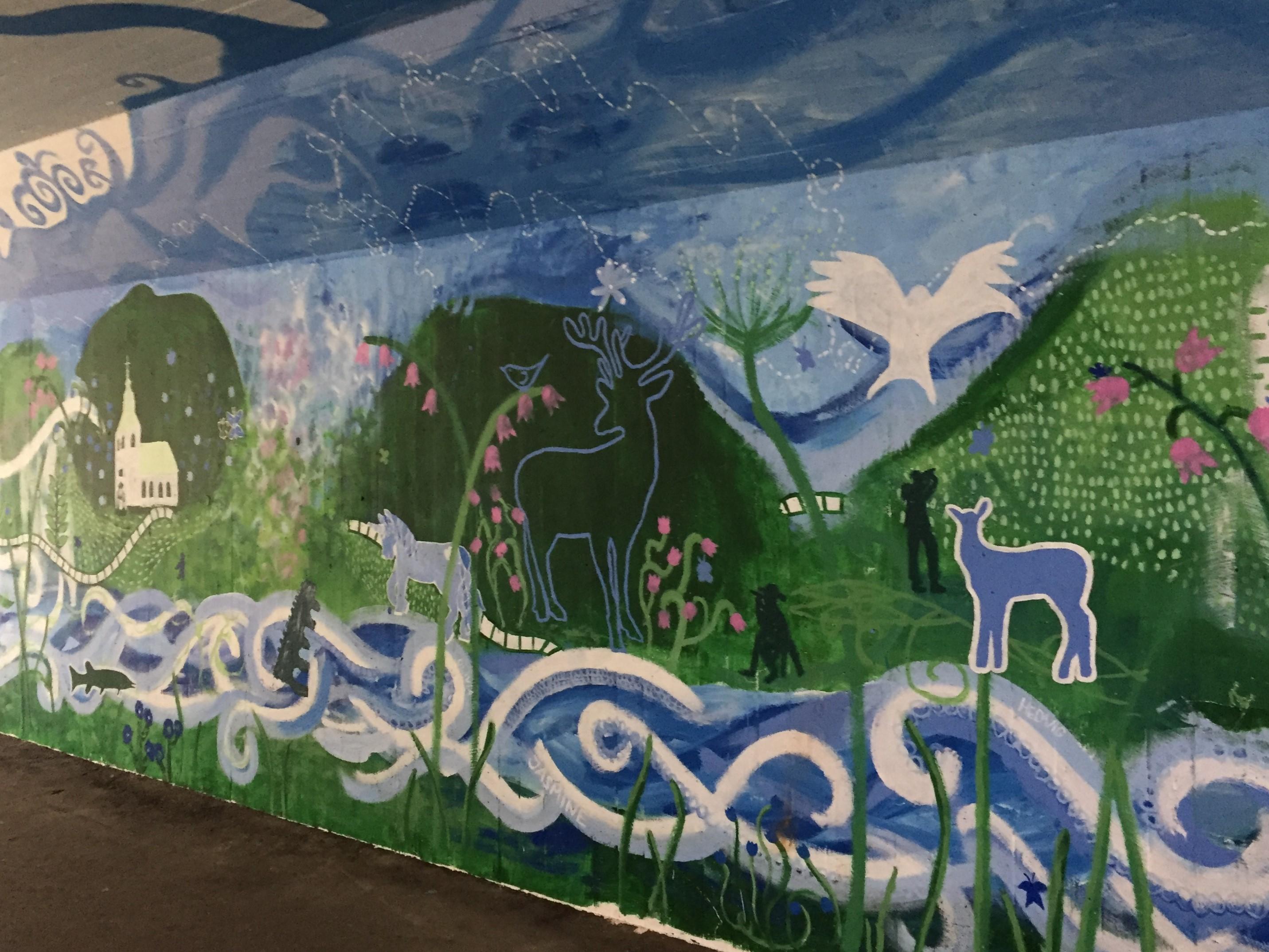 Väggmålning med gröna kullar och bäck.