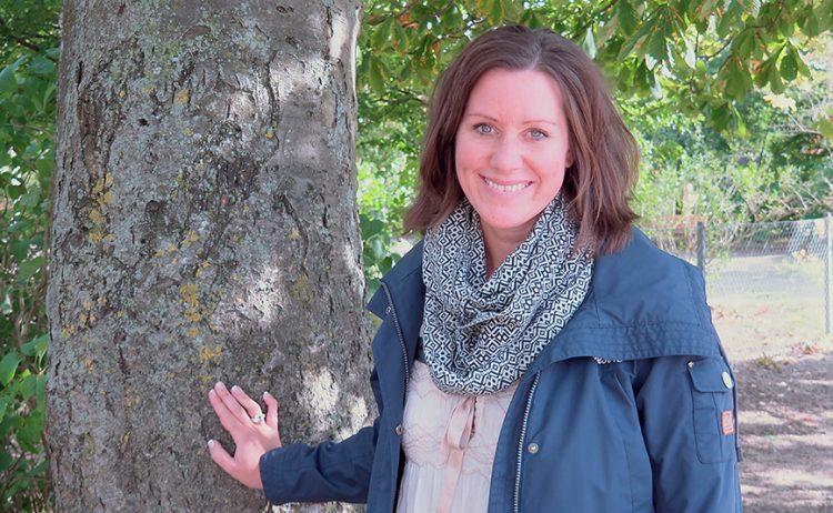 Kvinna står vid träd.