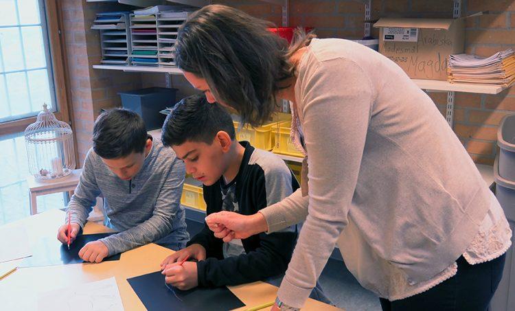 Kvinna hjälper två elever vid skrivbord.