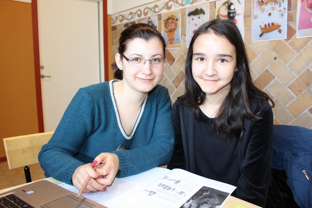 Två flickor sitter i korridor och jobbar.