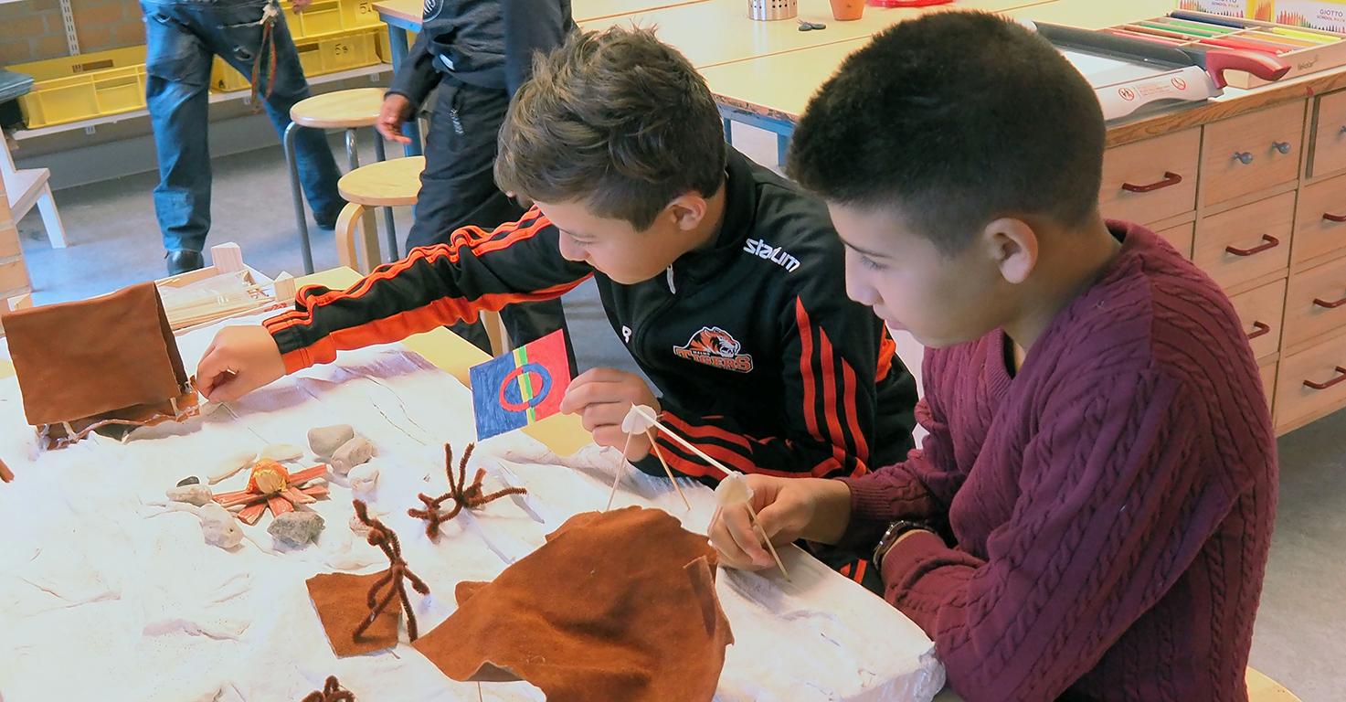Två elever pysslar ihop samelandskap.
