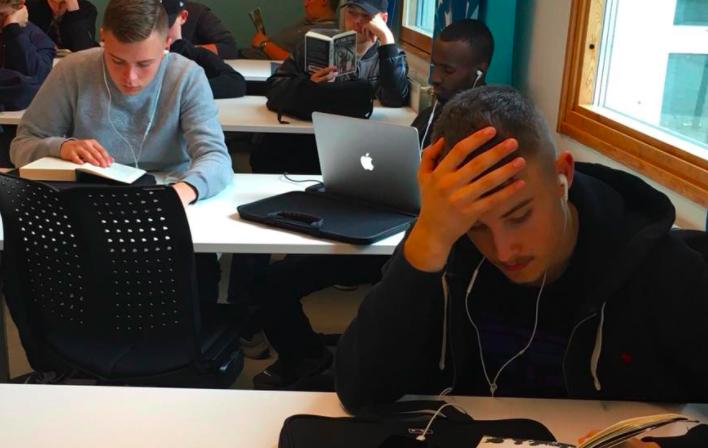 Elever läser och sitter vid datorn i klassrum.