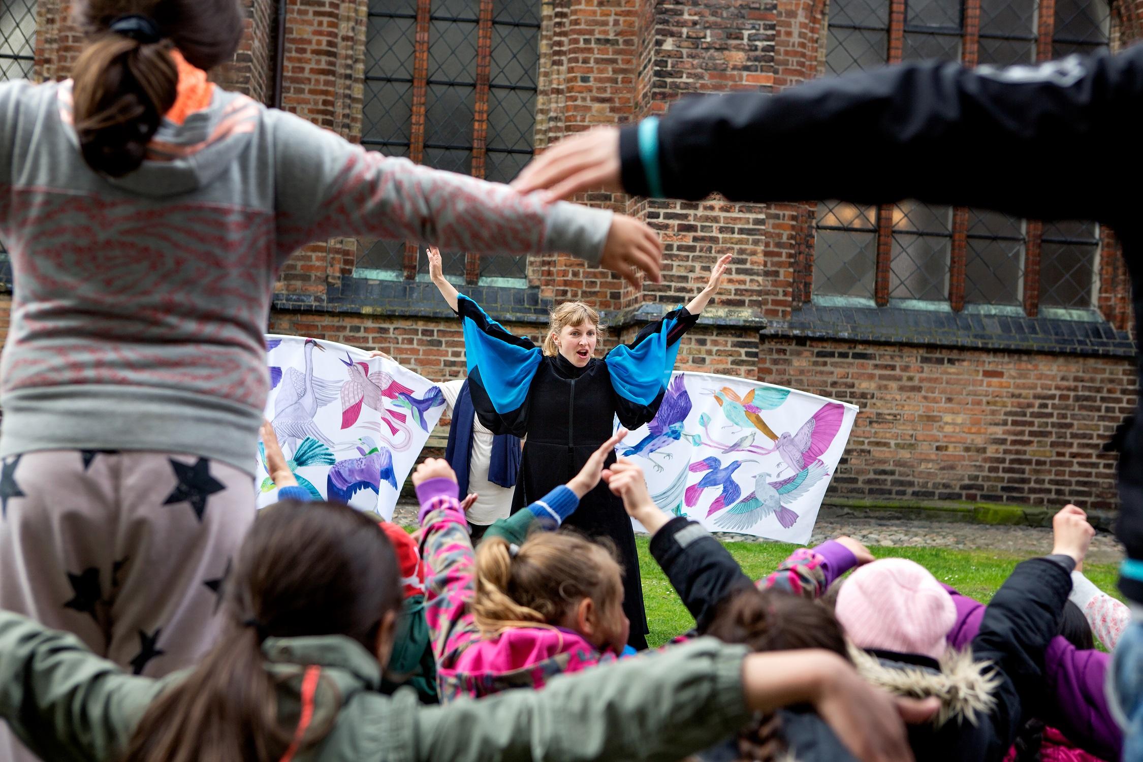 Kvinna och barn sträcker på armarna.