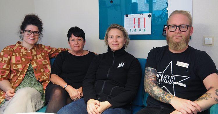 Fyra personer sitter i soffa.