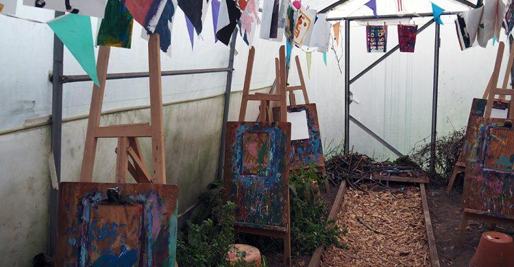 Växthus med teckningar hängandes i luften och staffli uppställda.