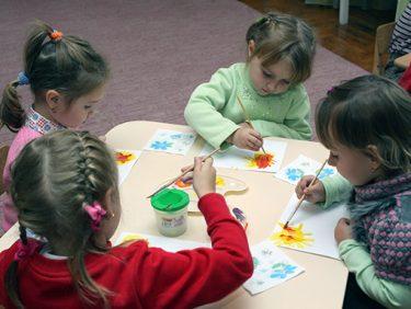 Fyra barn målar med färger.