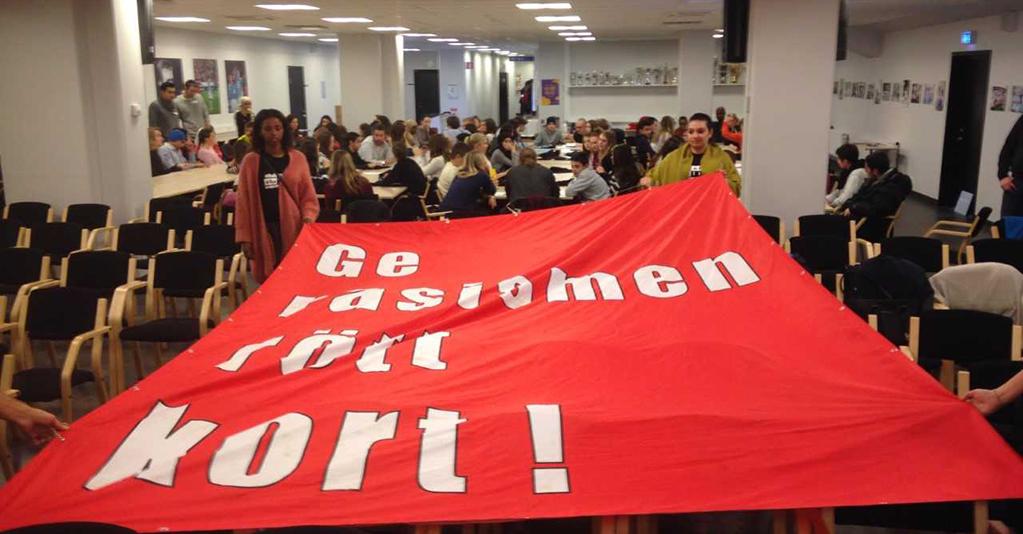 Elever håller upp röd flagga där det står ge rött kort åt rasismen.