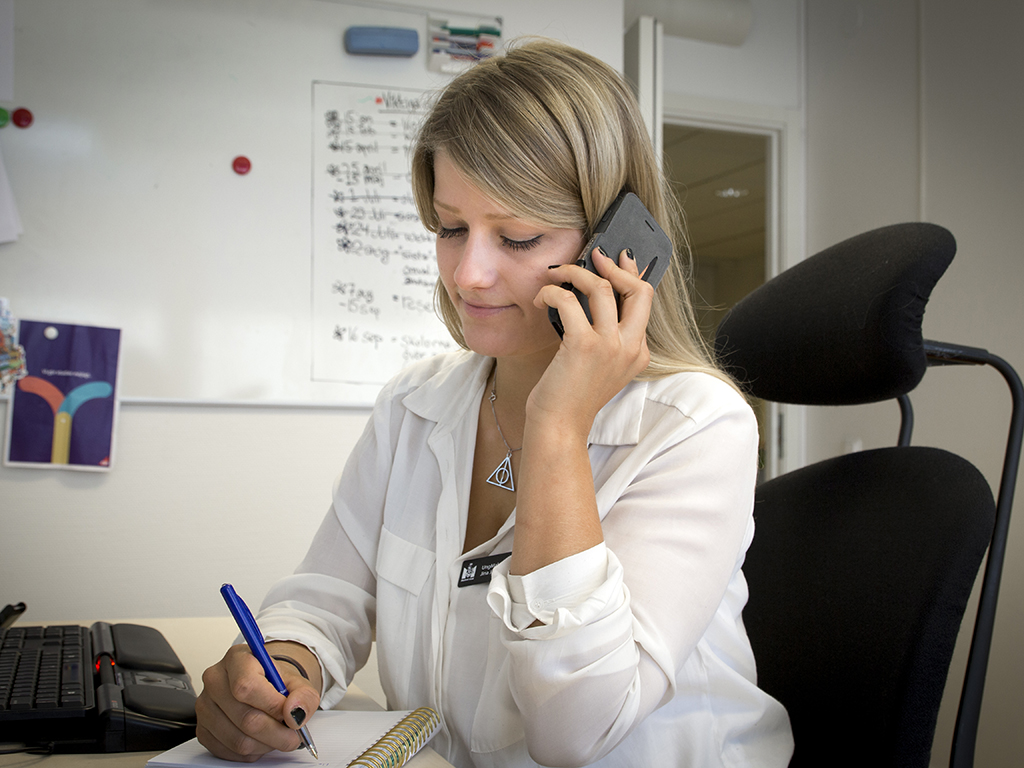 Kvinna antecknar samtidigt som hon pratar i telefon.