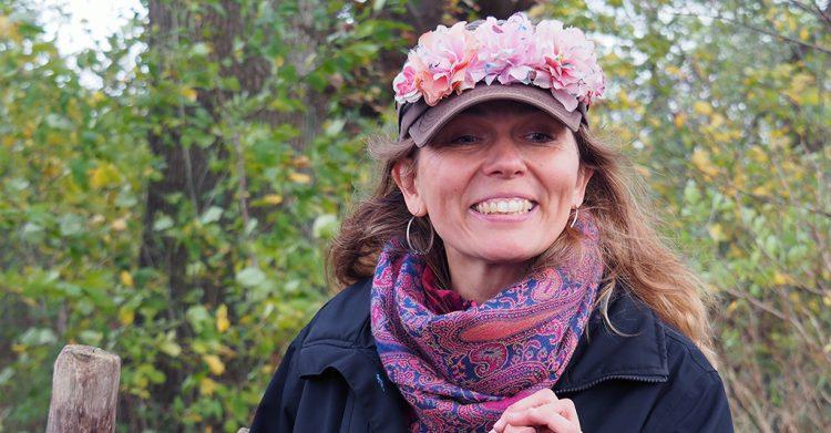 Kvinna med blommor i sin keps.