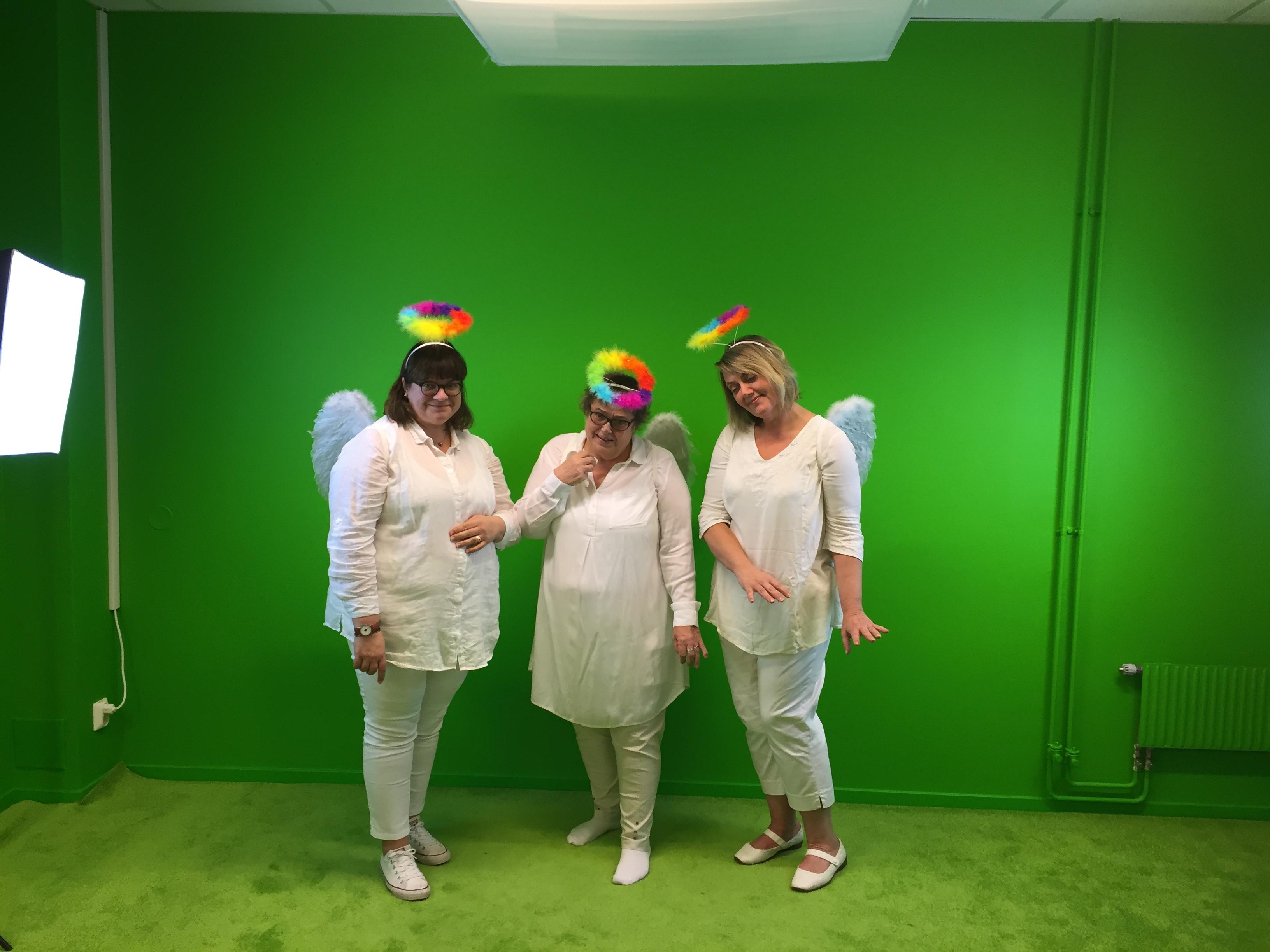 Tre kvinnor utklädda till änglar framför grön vägg.