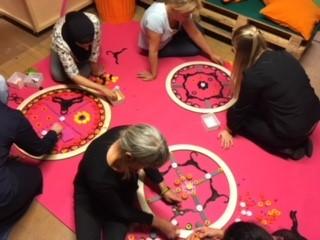Personer sitter på golvet och gör cirklar.