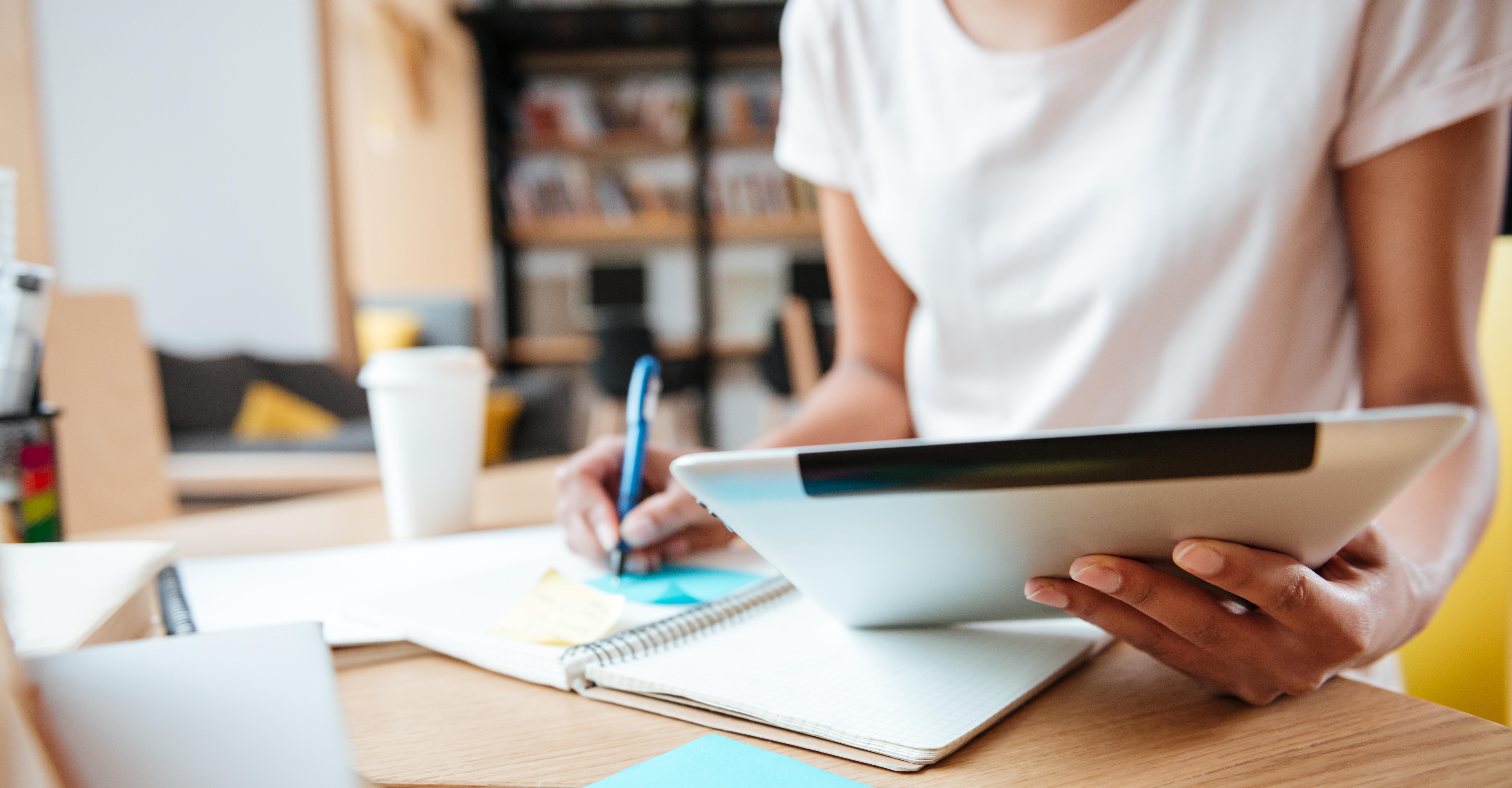 Kvinna håller läsplatta i handen och antecknar samtidigt i block.