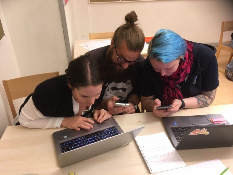 Tre personer sitter med datorer och mobiler.