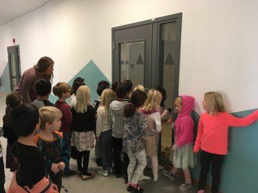 Barn kikar in genom dörr.