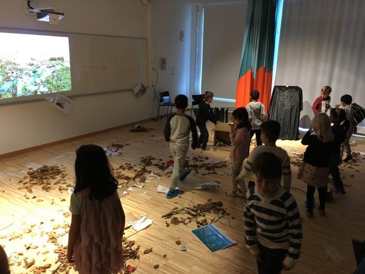 Barn med massor av naturmaterial framför sig på golvet.