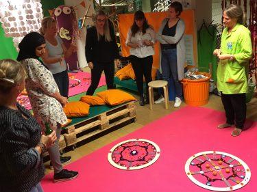 Personer tittar på cirklar på golvet.