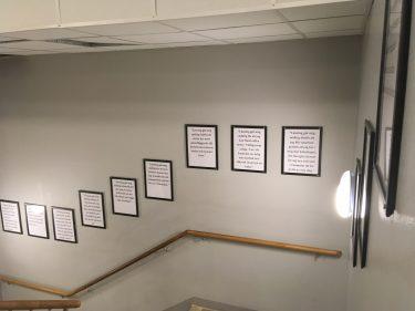 Flera tavlor sitter uppe på väggen i trappan.