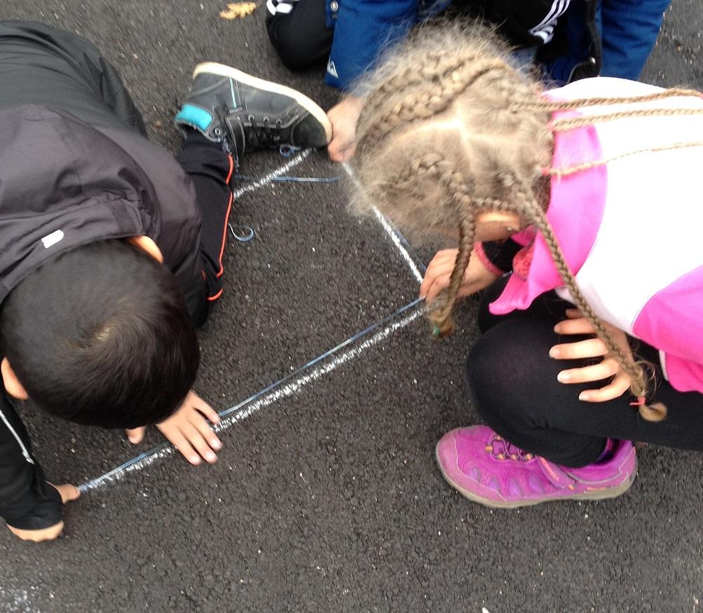 Två elever mäter och målar med krita på marken.