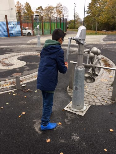 Pojke pumpar vatten ur pump.