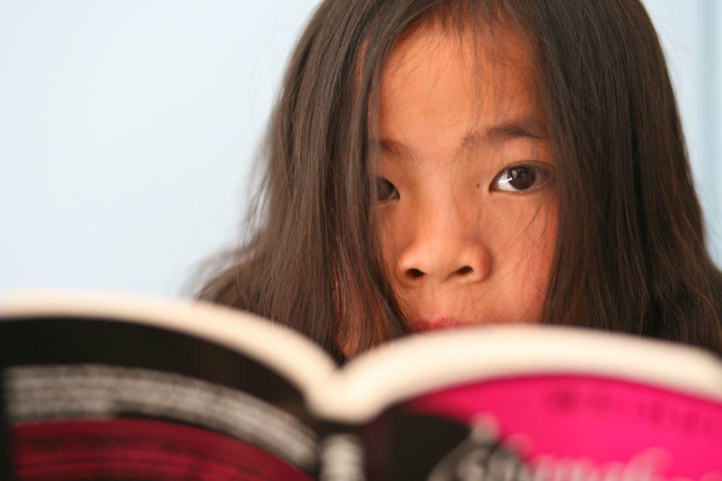 Barn läser i uppslagen bok.