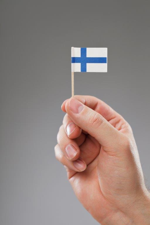 Hand håller upp finsk flagga.