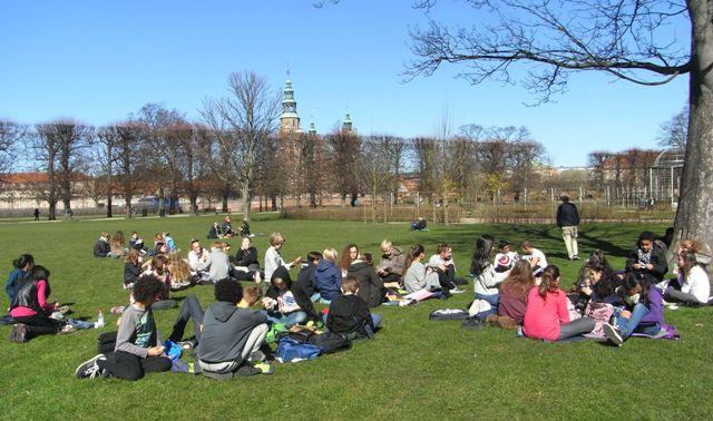 Elever sitter i gräset och pratar.