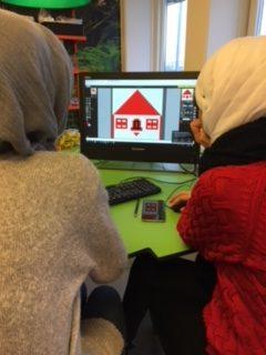 Elever ritar hus på dator.