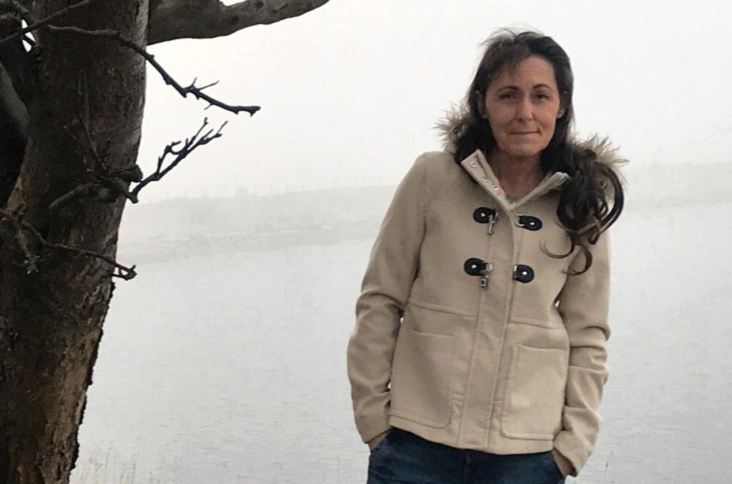 Maria Friberg, Biträdande förskolechef på Gottorps förskola, står vid ett träd med hav i bakgrunden.