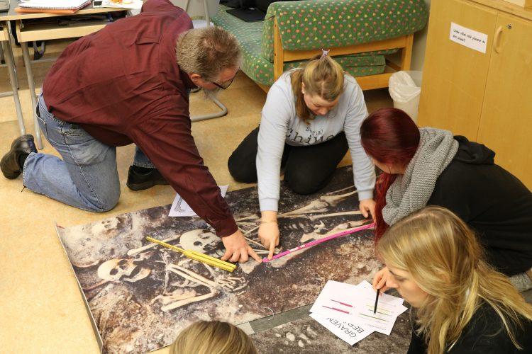 Elev mäter skelett från matta där ett skelett är avbildat.
