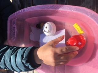 Hand testar om olika föremål flyter.