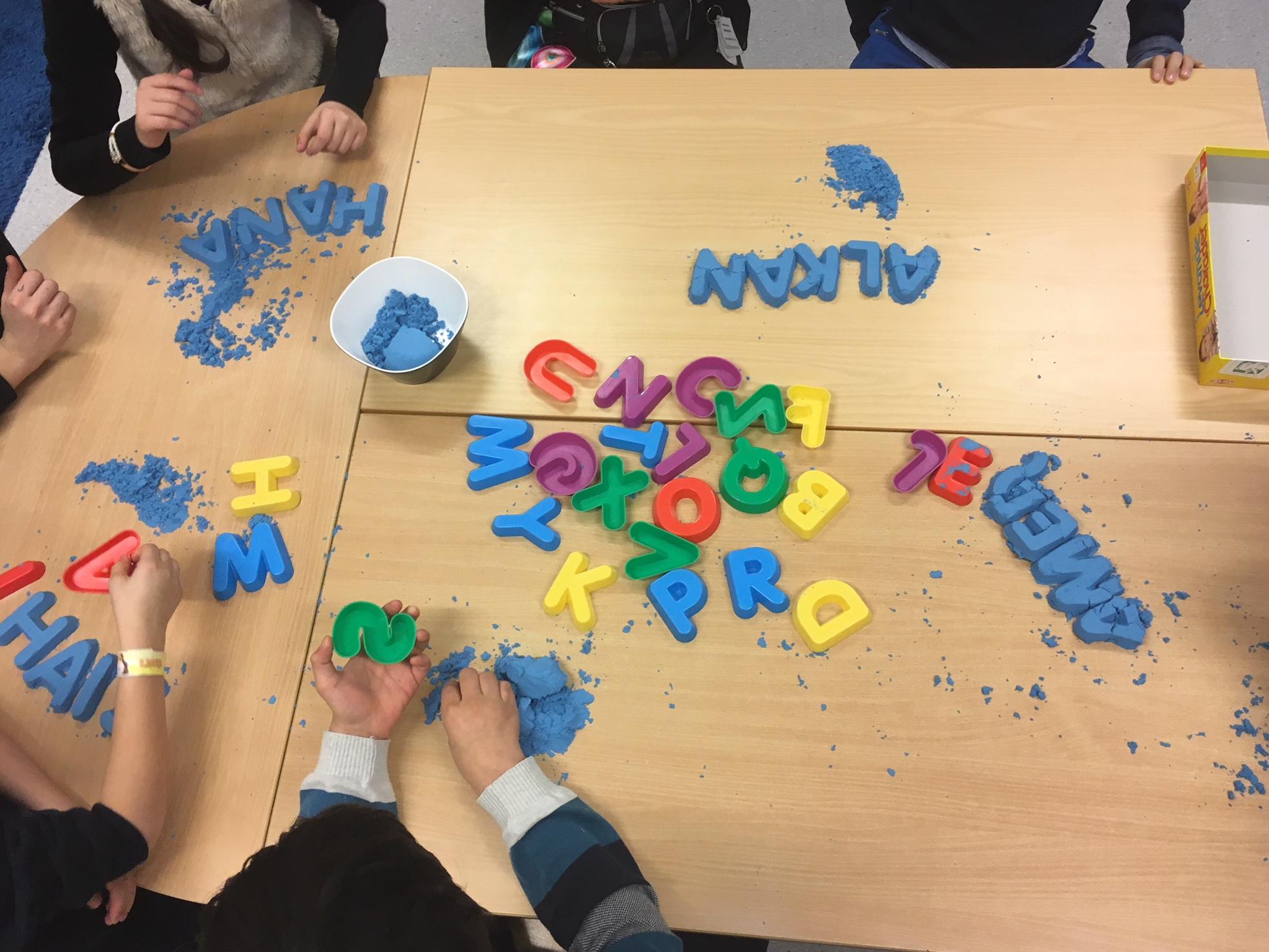 Barnhänder leker med lera och bokstavsformer.