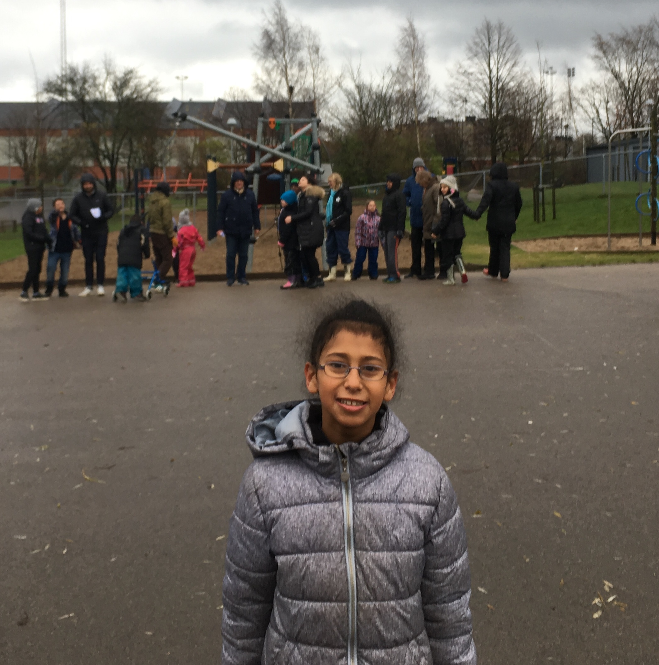 Elev står på skolgård där andra barn leker.