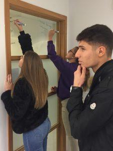 Elever skriver på glasruta.