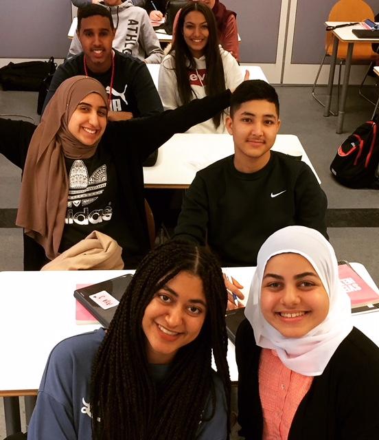 Glada elever sitter i klassrum i skolbänkarna.