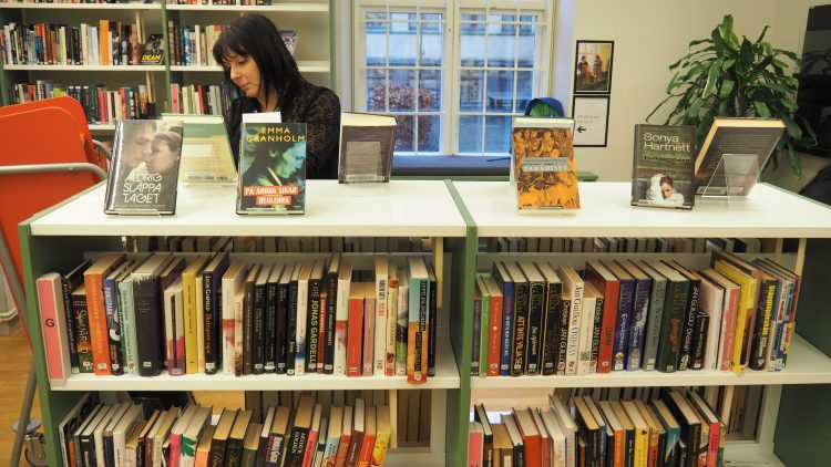 Eva Akenine, bibliotekarie på Pauliskolan, sorterar böcker i skolbiblioteket.
