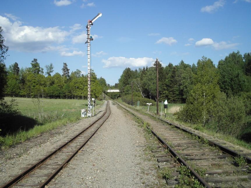 Järnväg som leder in i skogen.