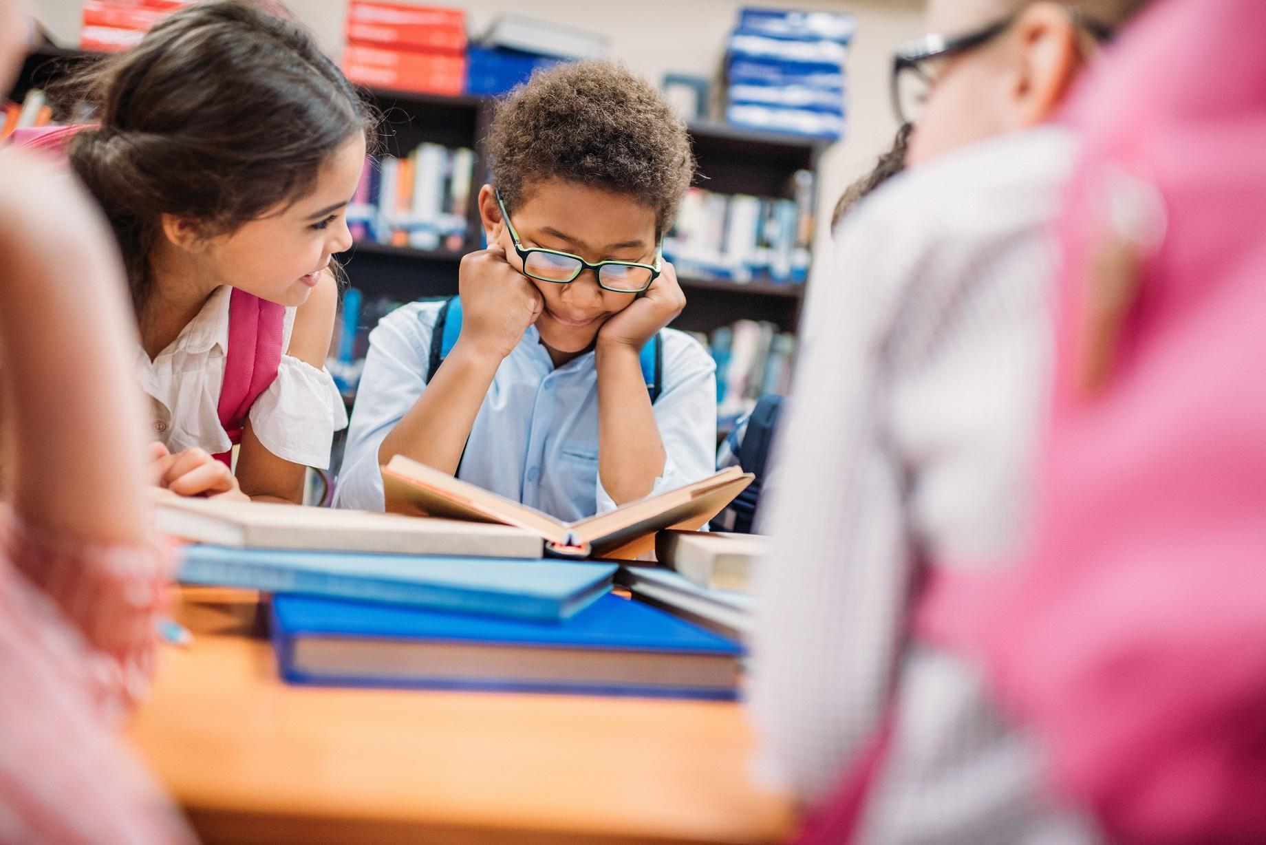 Barn läser i skolbibliotek.
