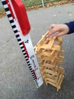 Hand bygger torn av trästavar och linjal står bredvid för att mäta hur högt det blir.