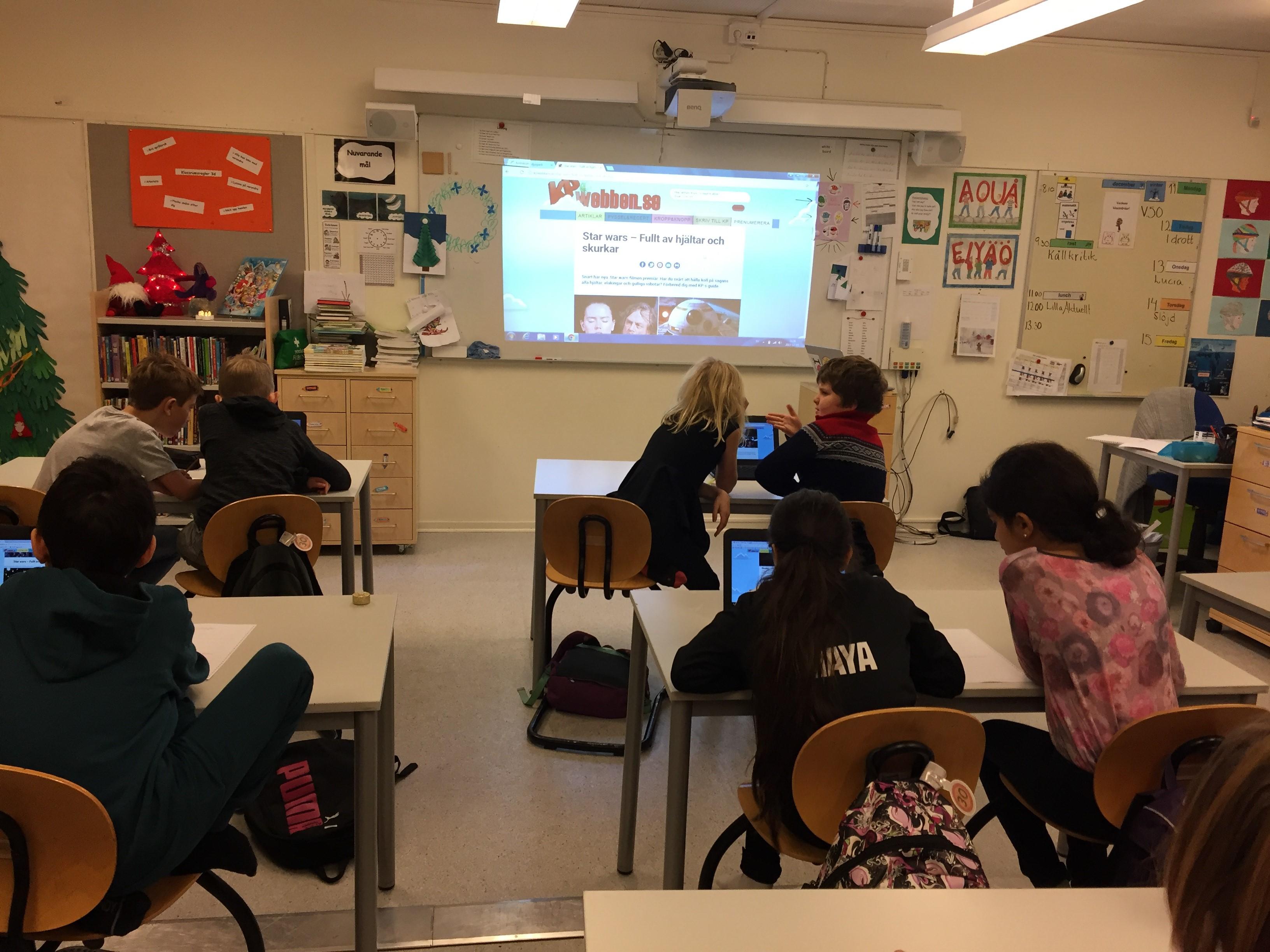 Elever sitter i klassrum sitter i bänkarna.