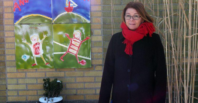 Kvinna framför konstverk på skolans vägg.