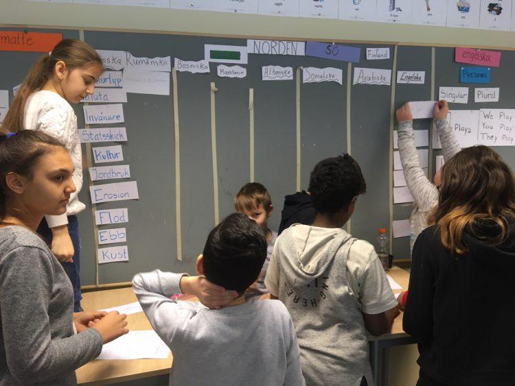 Elever sätter upp teckningar på väggen.