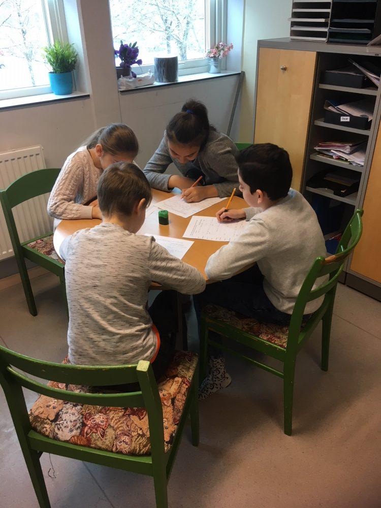 Elever sitter bord och skriver på papper.