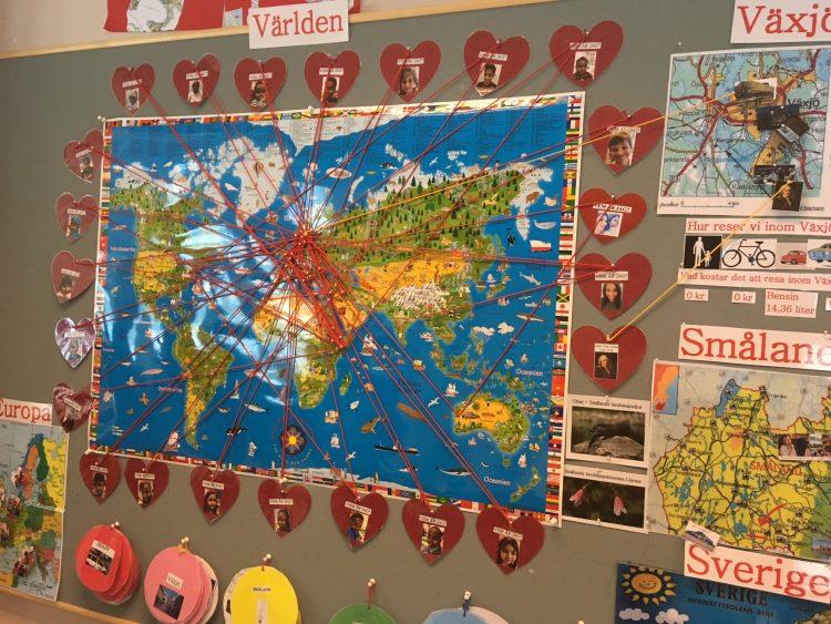 Hjärtan med elevers ansikte har tråd dragen till var de kommer ifrån på världskarta.