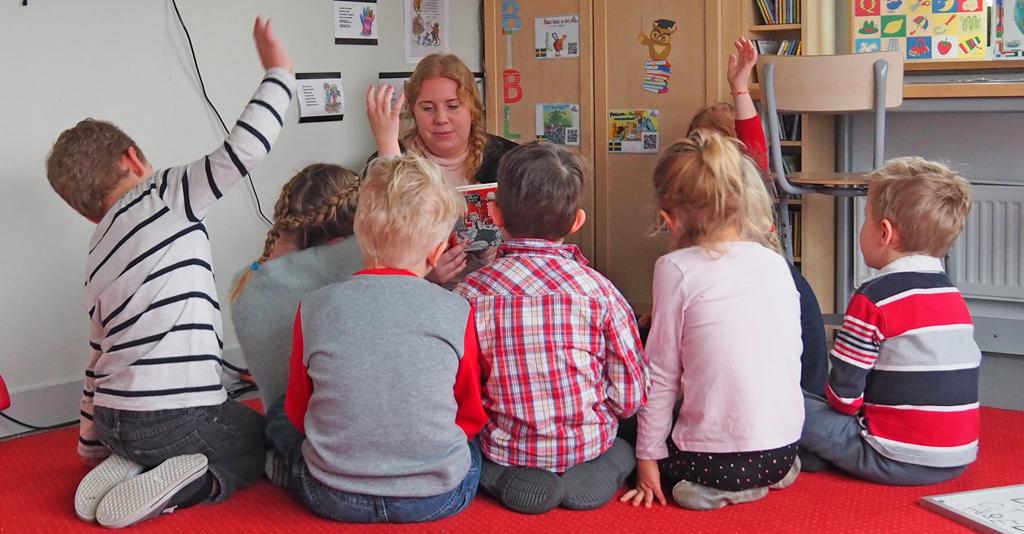 Kvinna läser bok framför barn som sitter på golvet.
